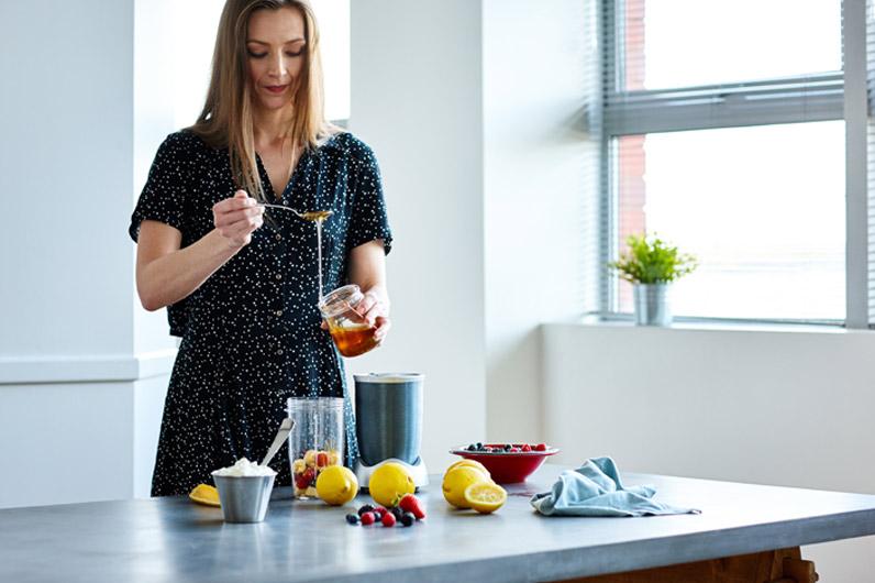 Mulher a utilizar mel na refeição